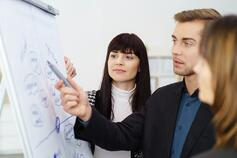 Young businessman having a serious discussion with two female co-workers as they stand together discussing a hand written flip chart.jpeg